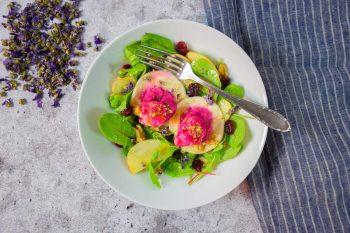 Rote Rüben-Nudl auf buntem Salat mit Äpfeln und Cranberries